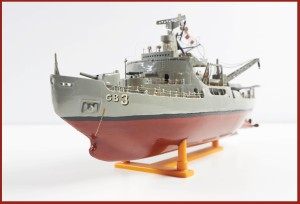 A highly detailed model of a navy wind-class icebreaker ship. Below the water line the ship is painted red, while above it is a steel gray. The deck is littered with various apparatus such as guns, lifeboats, radar equipment, and cranes.